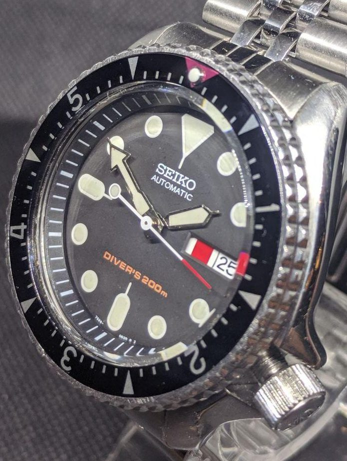 Seiko Mod by WellingTime UK. Seiko SKX007 Vintage Seamaster Mod: This watch has been lightly modded to retail most of its original parts but to style it like a vintage omega seamaster. The watch includes the original Seiko SKX case, bezel dial & hour & minutes hands as well as the original Seiko 7S26 movement. The minimal modifications all have a hint of red to them. Including white counter balance second hand with red tipped point and vintage seamaster style bezel with red triangle mounted with a pearl of lume. Fitted with a jubilee strap.