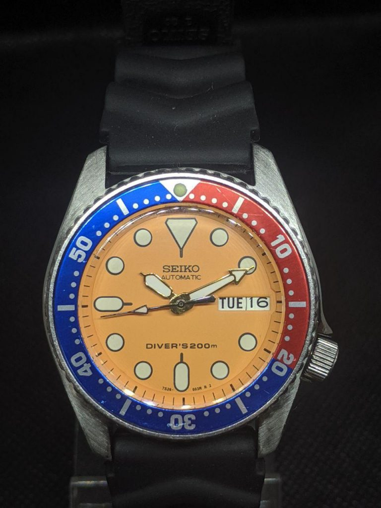 Seiko Mod by WellingTime UK. Seiko SKX013 - Tangoed mod: This mod the orignal stainles case, bezel, crown.It has been modified to include a replacement orange SKX013 dial and chapter ring, Polished Gold plated SKX hands and a pepsi bezel insert