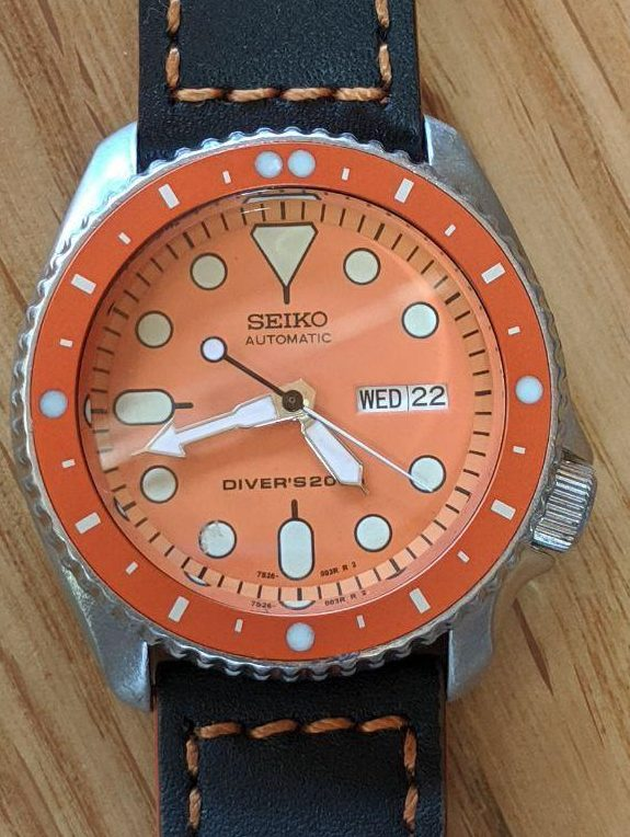 Seiko Mod by Wel lingTime UK.  Seiko SKX007 Tangoed Mod: Orange SKX dial., orange chapter ring, polished gold SKX hands, flat sapphire crystal with beveled edge.Black leather watch strap with Thick Orange Stitching