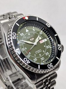 Seiko Mod by WellingTime UK. Seiko SKX007  Green SNK Military Mod: This mod features the SNK military seiko dial and hands set, with a ceramic bezel insert that includes a  red triangle & pearl of lume at noon. The watch is in the original Seiko Stainless steel case with original bezel and jubilee bracelet.