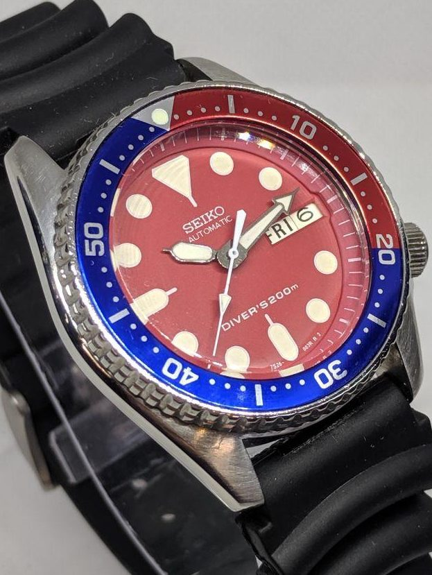 Seiko Mod by WellingTime UK. Seiko SKX013 - Red Mod:  The watch is fitted with a red SKX013 dial with a matching red chapter ring with white minute markers. The hands are in the SKX13 style with a White lume. The stainless steel watch case and bezel have been brushed and polished. The watch is finished with a genuine SKX013 Pepsi Bezel insert.The strap is a 2 peice Seiko Silicone Z22 Divers Strap.