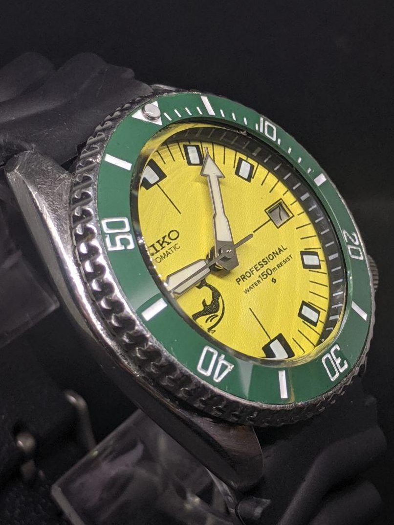 Seiko Mod by WellingTime UK. Seiko 7002 - SOXA mod:   Ceramic green insert, double dome sapphire crystal with clear AR coating, yellow whale dial, polished Seiko Diver hands. Black chapter ring with white minute markers. The watch is fitted with a Seiko Z22 Silicone Strap.