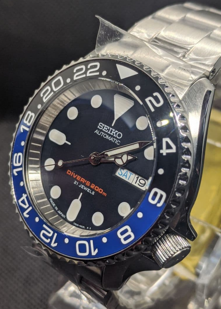 Seiko Mod by WellingTime UK. Batman Submariner SKX Mod: Double dome sapphire crystal with blue AR coating, brushed stainless steel chapter ring with etched minute markers, batman bezel insert black and blue in colour with GMT markings, submariner bezel, polished mercedes hands with BGW9 Lume, a Seiko 4R36 movement, Oyster Bracelet with RLX Deployment Clasp and an S signed crown.