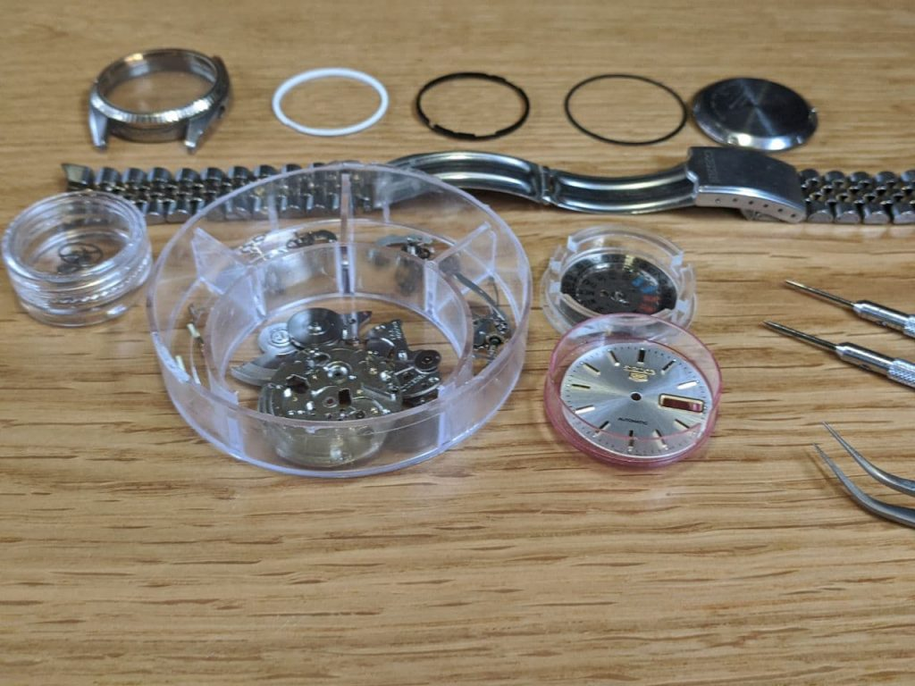 Wellingtime UK Watch Repair service - Watch Strip Down,  all components parts after they have been cleaned for watch repair. The dial, day/date wheel, balance wheel, case, dial spacer, movement holder, gasket caseback gasket and jubilee bracelet can all be seen individually spaced out in the centre there is a parts box which contains all of the watch movement component parts for repair. All work undertaken in the UK.