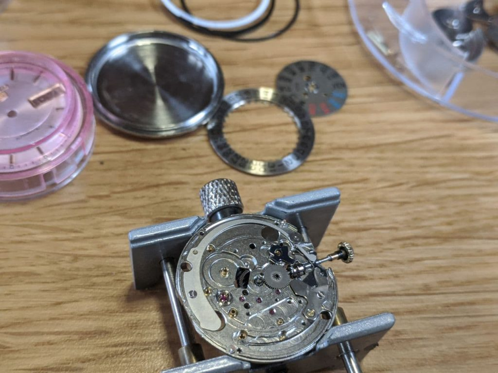 UK Watch Repair service - Disassembly of watch movement so repairs can be made to the watch. DateJust Seiko 7009 is featured in this photo, the movement is stainless steel, above the movement in the photo are the date & day wheel along with the dial and case back.