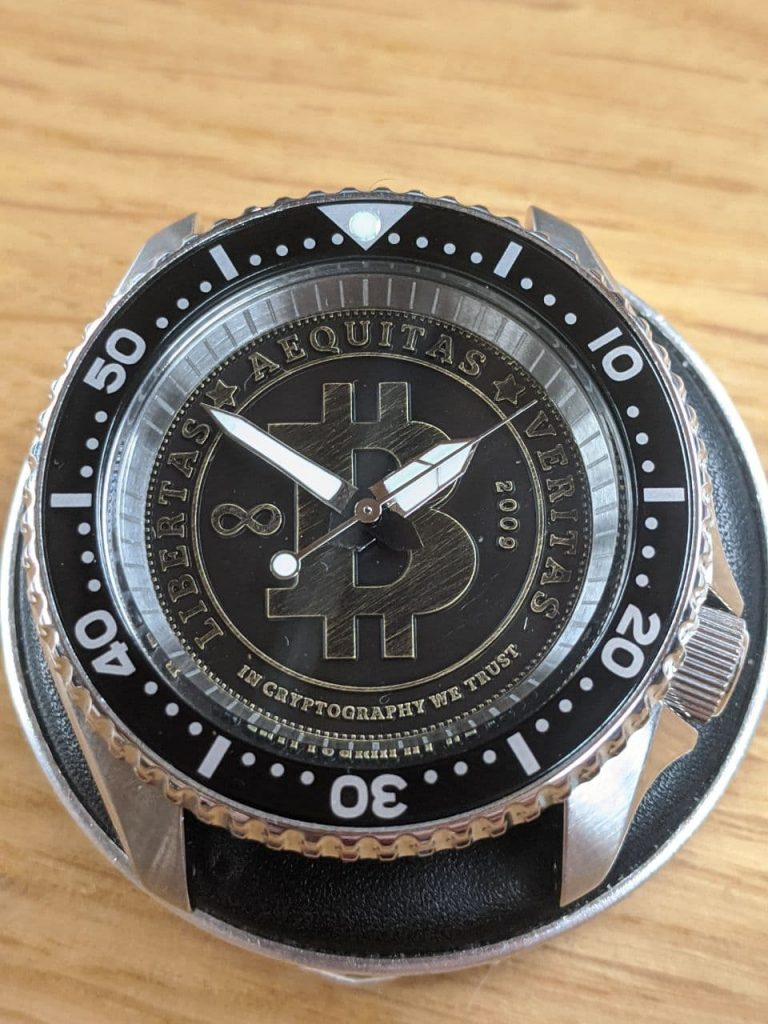 Bitcoin Dive Watch - Seiko Mod SPRD, Stainless steel chapter ring with etched minute markers, flat sapphire crystal, Black Bezel insert and seiko sea urchin hands. Displayed on a watch makers cushion.