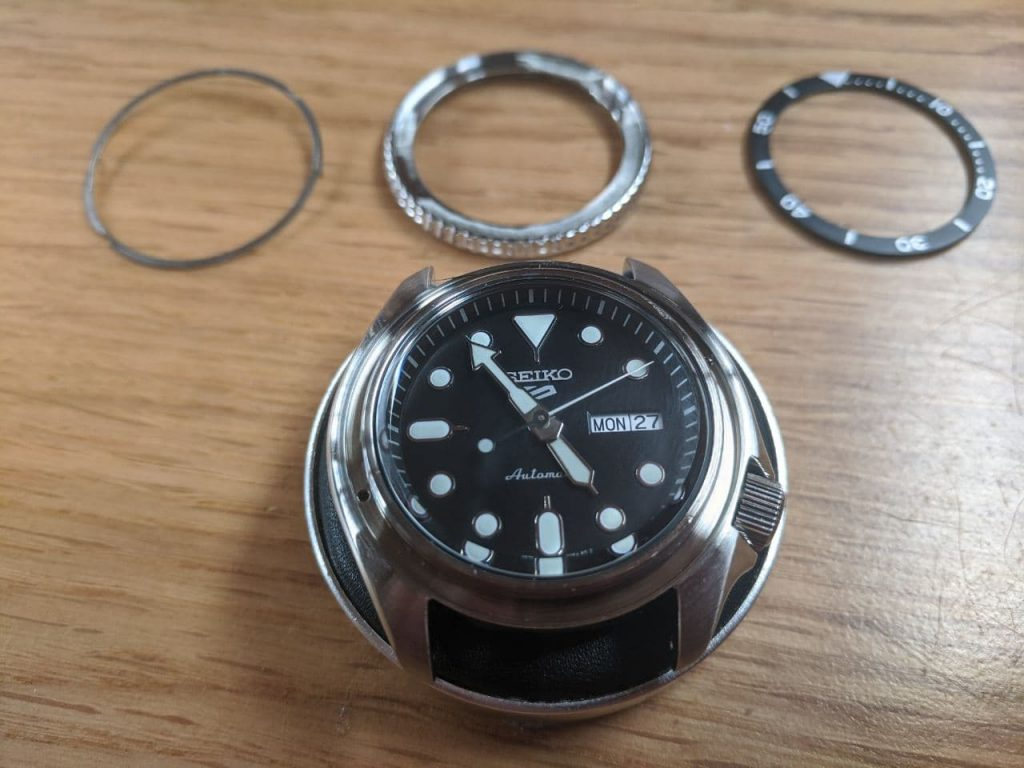 Seiko modification Process - Seiko SRPD55 Diver watch. Stainless Steel with black dial, displayed on a watchmakers cushion with the bezel and insert separated (parted) and the bezel click spring along. side. The watch sits centre front.  Seiko Bezel stip down, insert replacement.