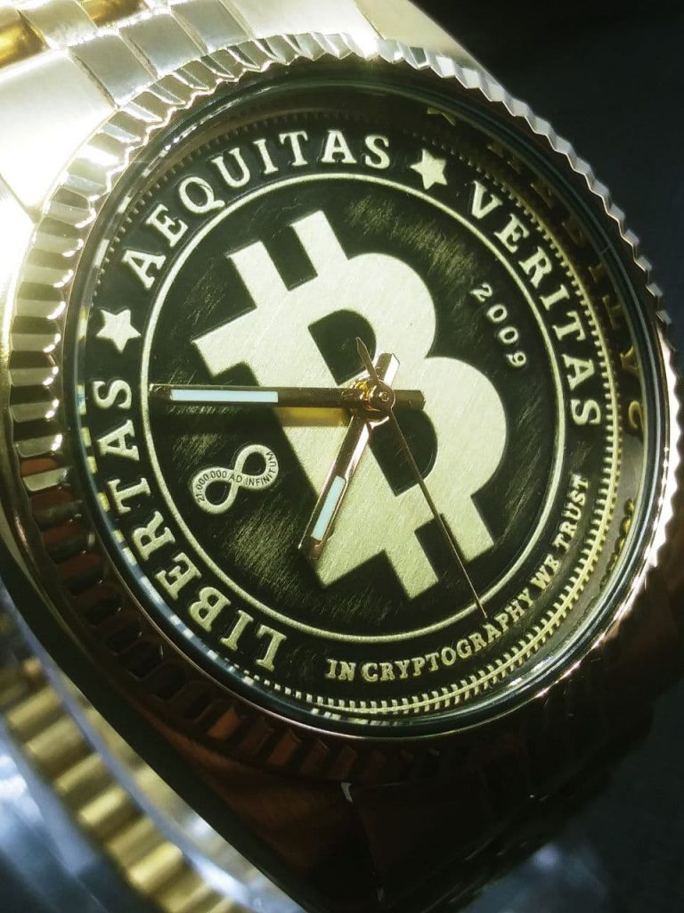 The dial is styled like circulated coin the raised areas are gold coloured with a brushed finish and the lower pressed arease are black with a light brushing of gold colour. The dial reads, Libertas,  Aequitas, Veritas, In cryptography we trust dated 2009 when bitcoin was born