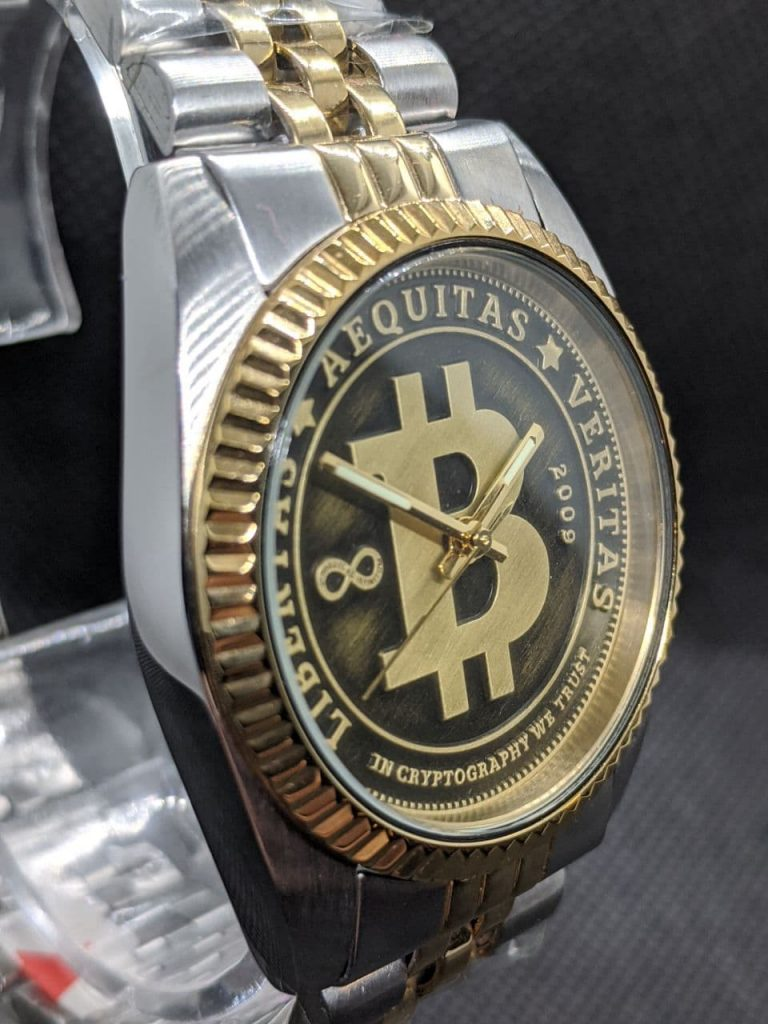 Bitcoin Watch - DateJust Styled Bitcoin Dial with Seiko NH36 Movement. Stainless Steel case and gold plated crown & fluted bezel. The watch is finished with a bi-metal coloured jubilee bracelet. The dial is styled like circulated coin the raised areas are gold coloured with a brushed finish and the lower pressed arease are black with a light brushing of gold colour. The dial reads, Libertas,  Aequitas, Veritas, In cryptography we trust dated 2009 when bitcoin was born