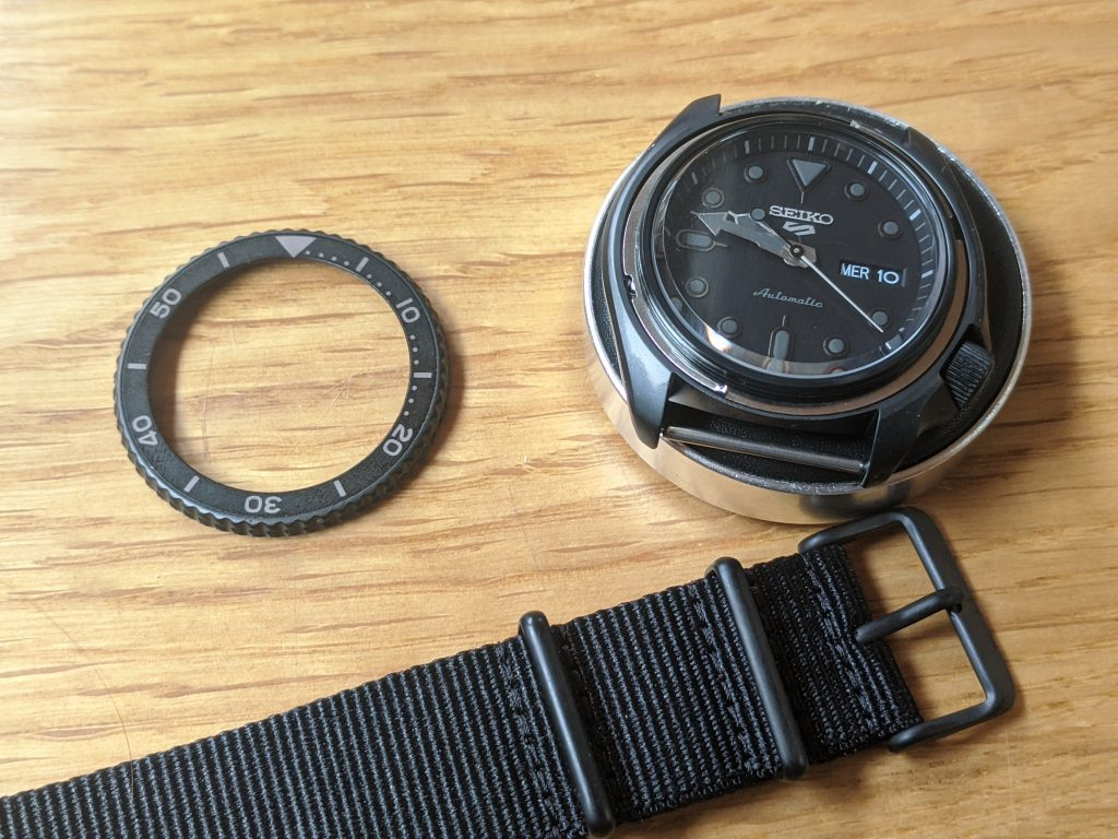 Seiko SRPD79 with Bezel removed (left), Displayed on a watchmakers cushion with the OEM NATO Strap, below.
