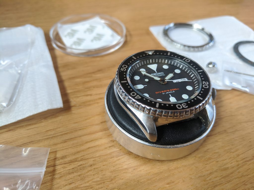 Seiko SKX007J displayed on a watchmakers cushion surrounded by parts ready to modify. Seiko Mods wellingtime