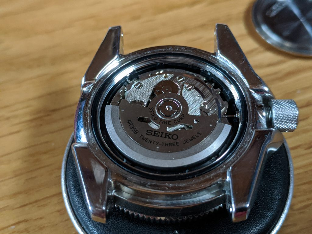 Seiko Samurai case back removed Exposing Seiko 4R35 Movement - displayed on watchmakers cushion.