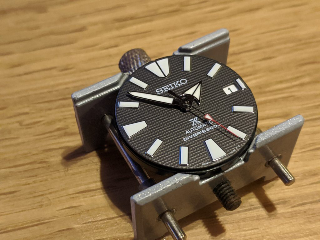 Seiko Samurai Waffle Dial, Movement & Hands displayed in a watchmakers movement holder. The watch hands have been repaired and reattached to the pinion of the Seiko 4R36 Movement .