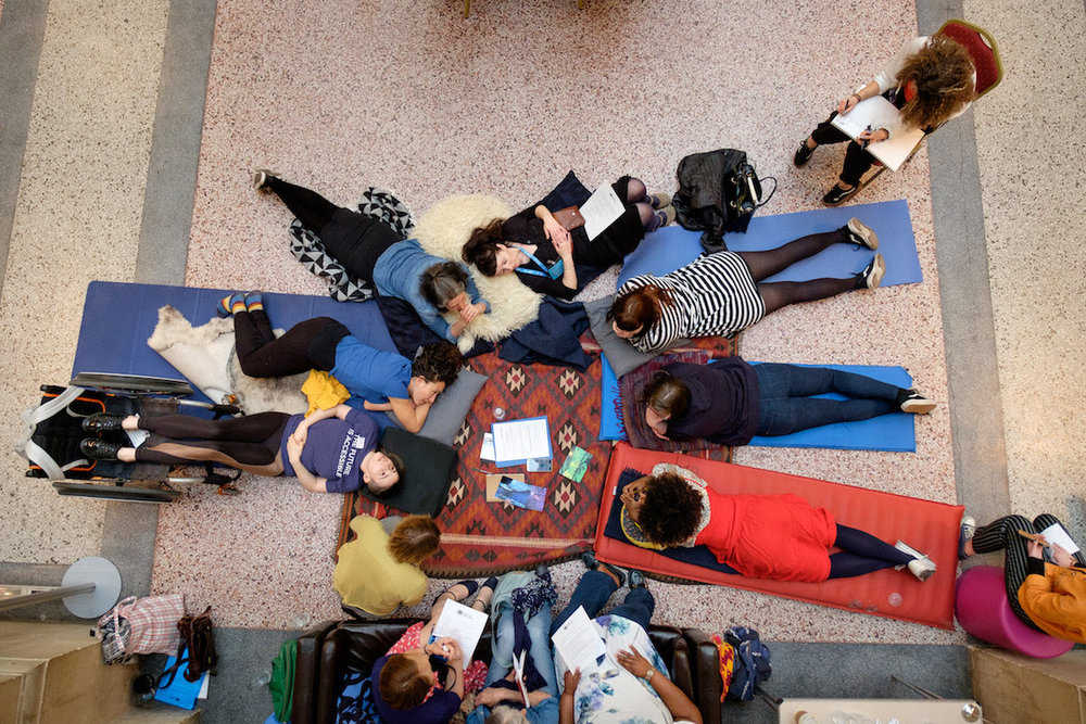 Image Description: This is a photograph taken from an aerial view perspective. On a hard floor, a group of people of varying age & ethnicity are lying on their fronts on top of some comfy looking yoga mats and cushions. They seems to be chatting and laughing with each other comfortably. Some are lying on their backs, some are sat upright, but all look like they have chosen their comfy positions.