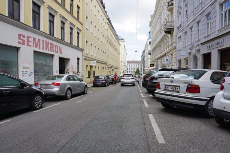 parkende Autos, fahrendes Auto und Radfahrer in der Otto-Bauer-Gasse, Wien-Mariahilf
