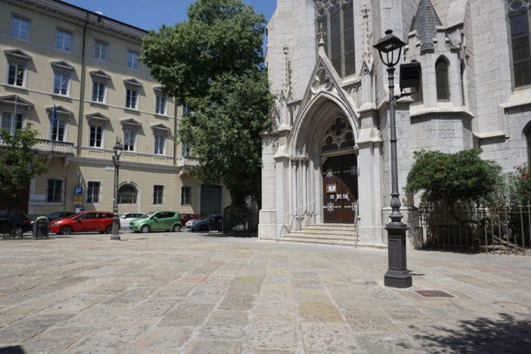 Platz mit Kirche, alten Straßenlaternen und Pflasterung in Triest, Italien