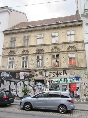 Biedermeierhaus in Wien-Neubau, renovierungsbedürftige Fassade, Autos
