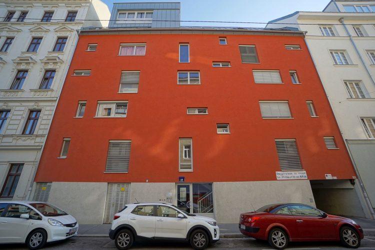 Wohnhaus mit orangener Fassade und kleinen Fenstern, Wien-Leopoldstadt