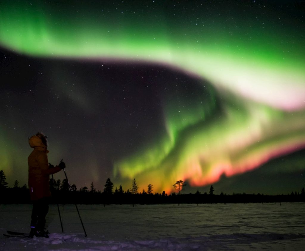 Person wathcing colourful northern lights above the frozen lake in lapland
