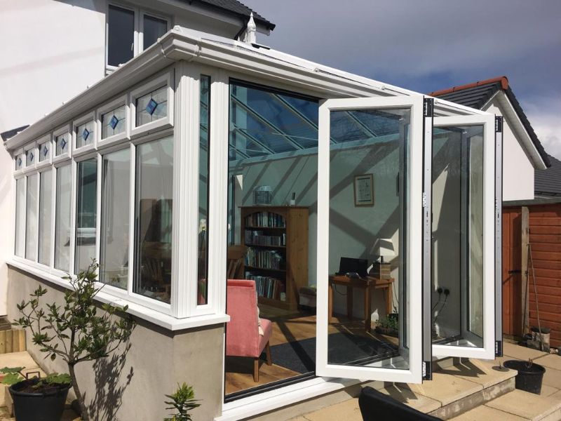 a modern style conservatory with bi-fold doors