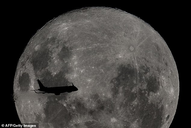 A plane from travelling towards the Argentine city of Bahia Blanca passes in front of a supermoon event, as seen from Buenos Aires, Argentina