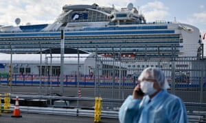 A man in protective gear speaks on the phone near the Diamond Princess cruise ship