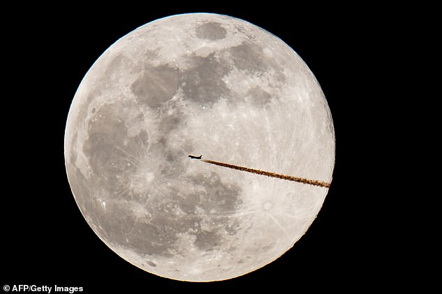 An airplane silhouettes against the last year's Snow Moon on February 19, 2019 in Nuremberg, southern Germany