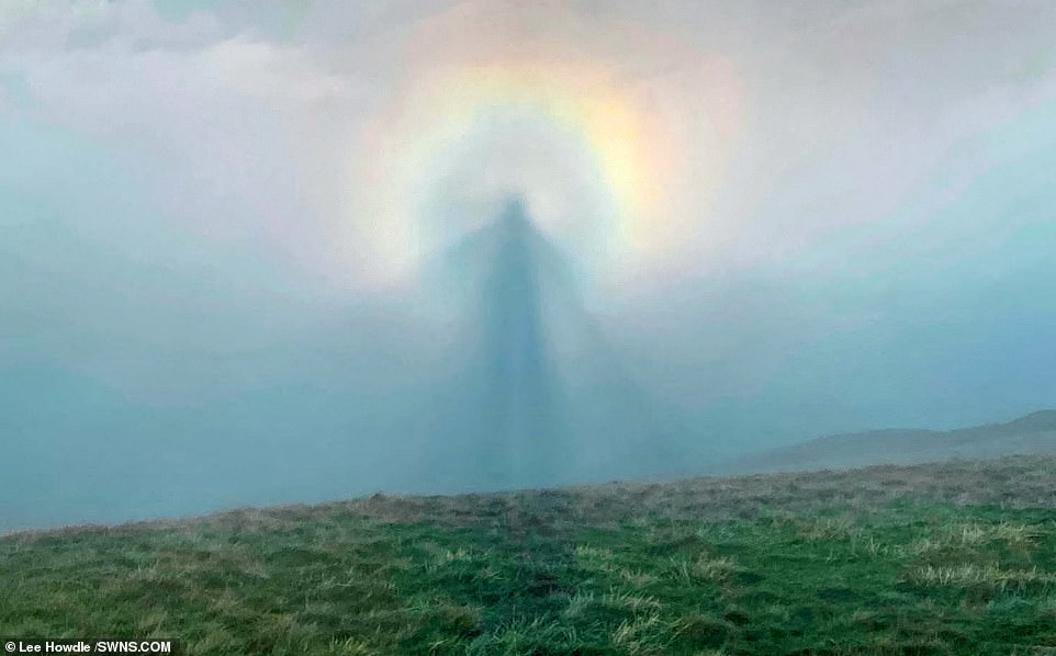 A photographer captured a magical scene while hiking in the UK this month– a phenomenon that appears to create an 'angel in the sky'. Lee Howdle was hiking through in the Peak District National Park in Derbyshire, central England where he encountered brocken specter