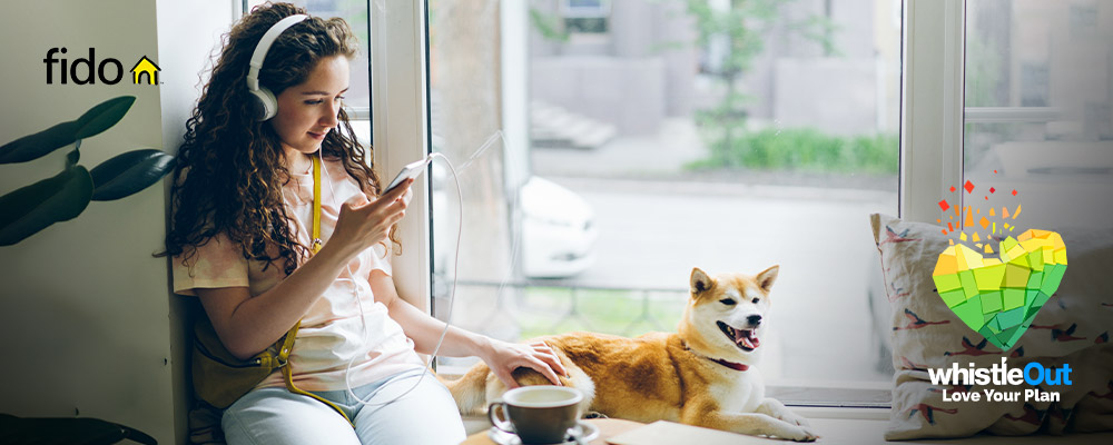 Woman looking at a smartphone with her dog beside her