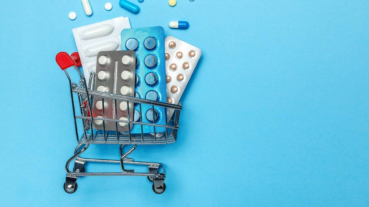 A small toy shopping cart filled with pills against a blue background.