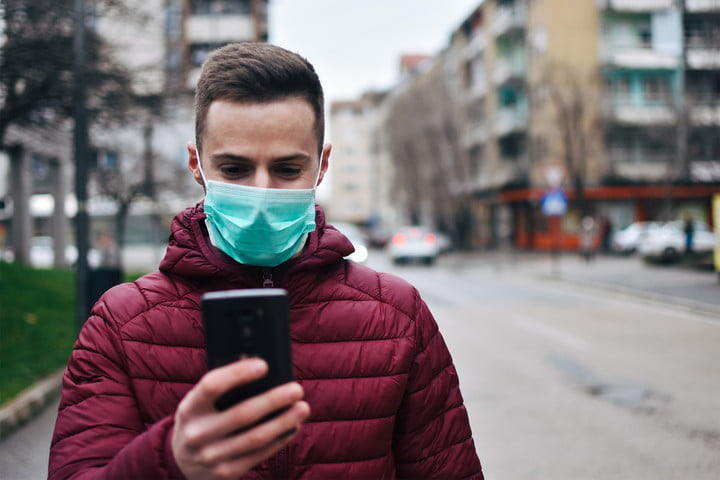 man checking phone with mask on