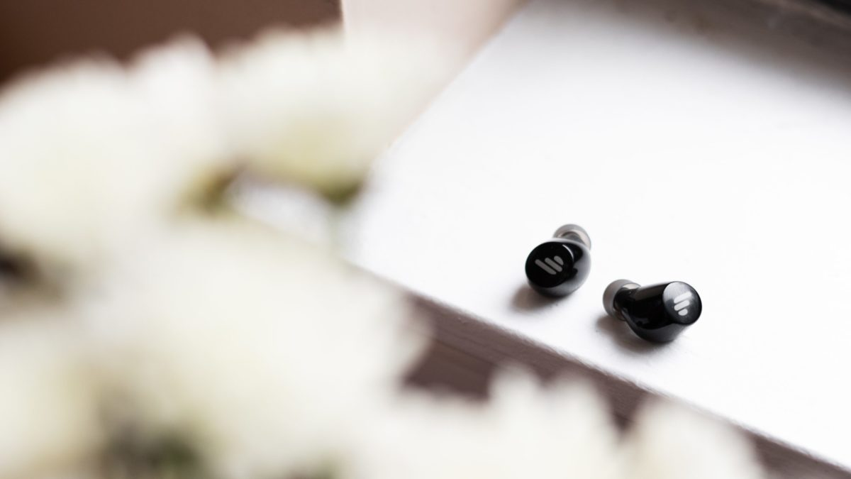 A picture of the Edifier TWS1 true wireless earbuds on a windowsill with flowers in the foreground.