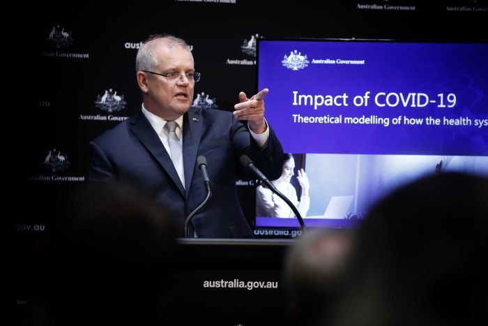 Scott Morrison stands in front of a screen with data about coronavirus. He points into the distance
