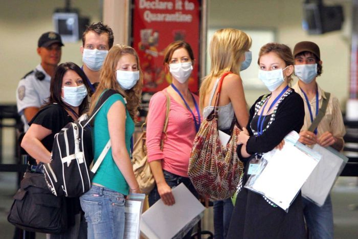 A group of passengers with face masks look at the camera.