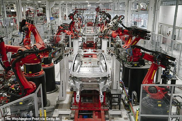 Robots work on a Tesla Model X in the factory in Fremont, California: Tesla is slashing employee pay and furloughing all hourly workers after the coronavirus pandemic forced the firm to shutter the plant