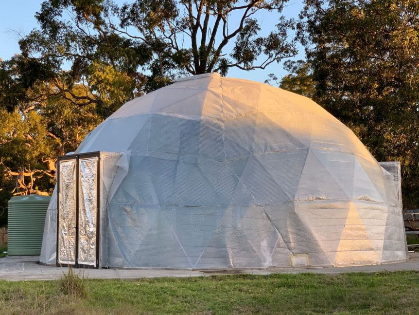A canvas dome on a lawn, with a metallic door inside.