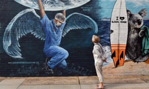 A woman looks at a mural of a health worker with wings holding a globe on International Nurses Day in Melbourne on 12 May 2020.