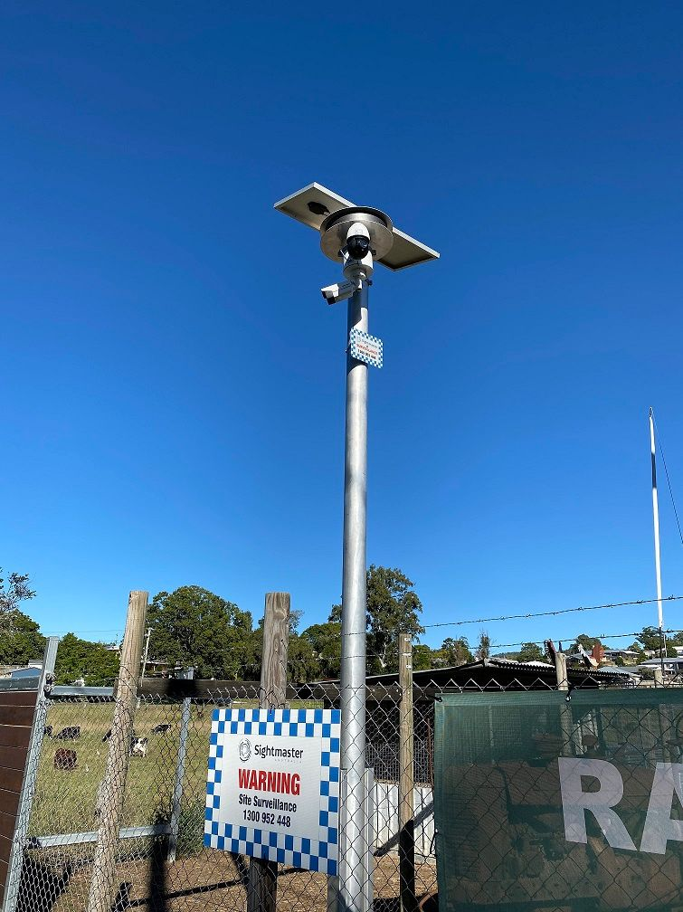 A number plate detecting security camera on a tall pole outdoors, with a blue sky behind.