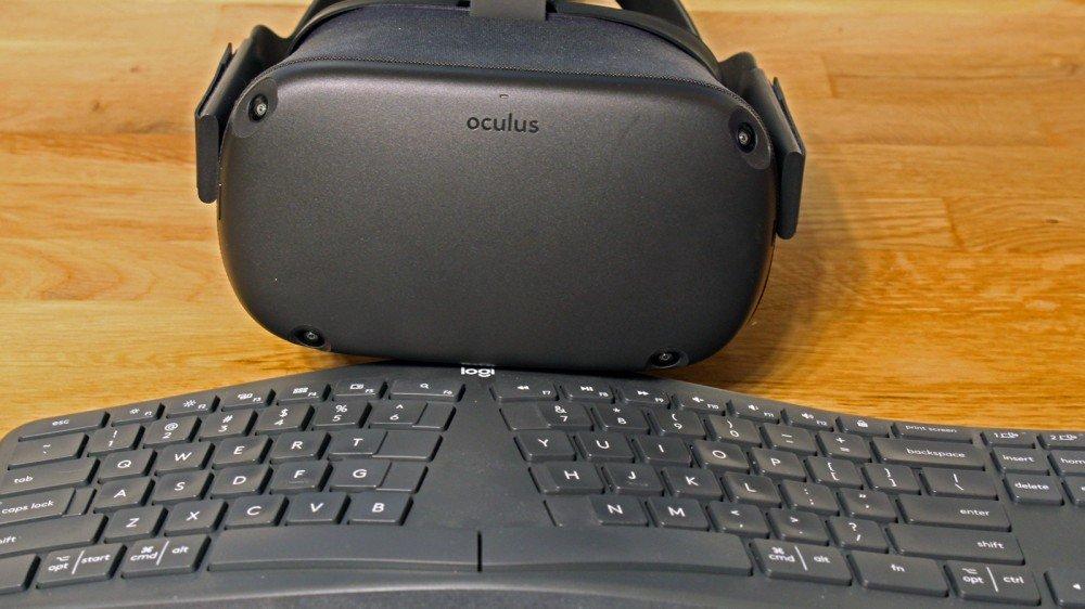 An Oculus Quest in front of a Logitech ergonomic keyboard.