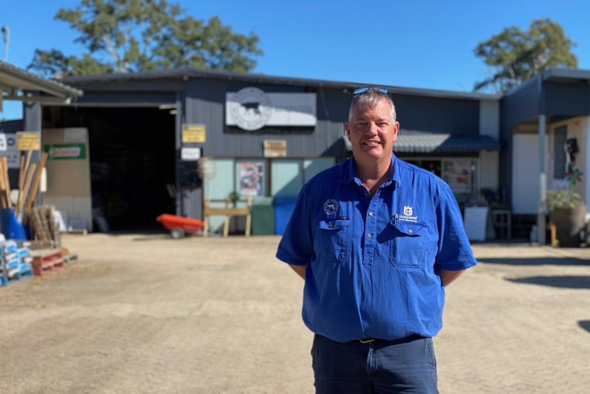 A man in a blue shirt standing outside a shed smiling.
