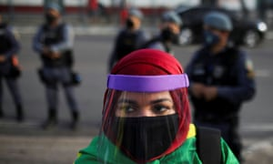 """A woman wearing a protective face mask and a protective face shield attends an anti-racism demonstration named """"Black and Indigenous Lives Matter"""" in Manaus, Brazil, 7 June 2020."""