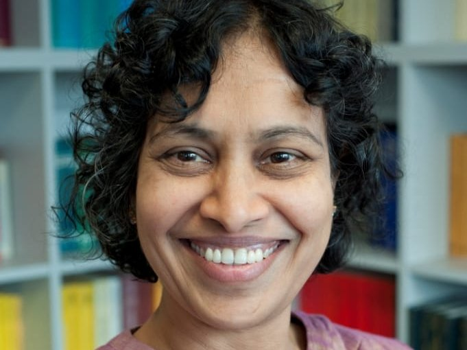 A smiling middle-aged woman of Indian origin wearing ethnic shift looks at camera in library.