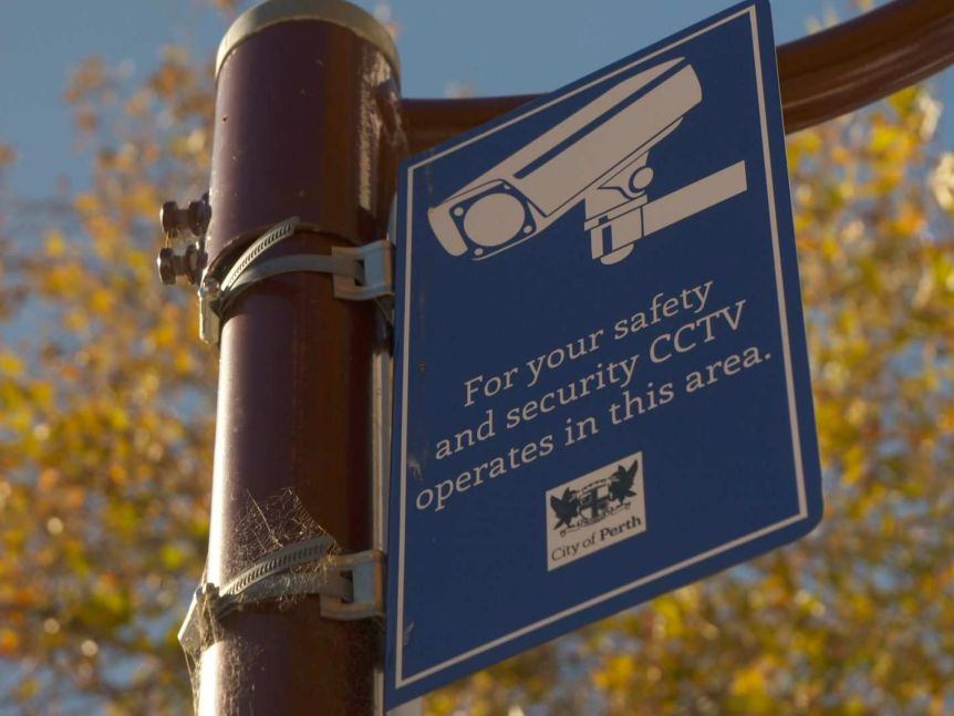 A sign on a lamp post warning people that CCTV operates in the area.