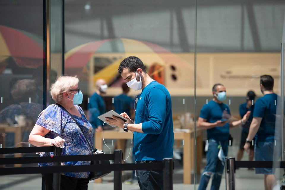 Apple Store interior with staff and customers wearing face masks