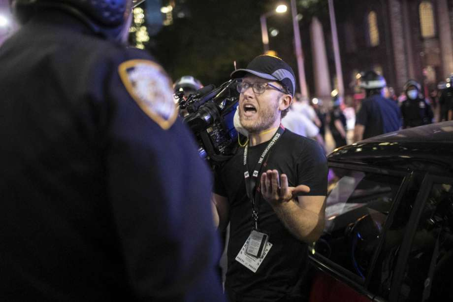 """Associated Press videojournalist Robert Bumsted reminds a police officer that the press are considered """"essential workers"""" and are allowed to be on the streets despite a curfew, Tuesday, June 2, 2020, in New York. New York City police officers surrounded, shoved and yelled expletives at two Associated Press journalists covering protests in the latest aggression against members of the media during a week of unrest around the country. Portions of the incident were captured on video by Bumsted, who was working with photographer Wong Maye-E to document the protests in lower Manhattan over the killing of George Floyd in Minneapolis. Photo: Wong Maye-E, AP / Copyright 2020 The Associated Press. All rights reserved."""