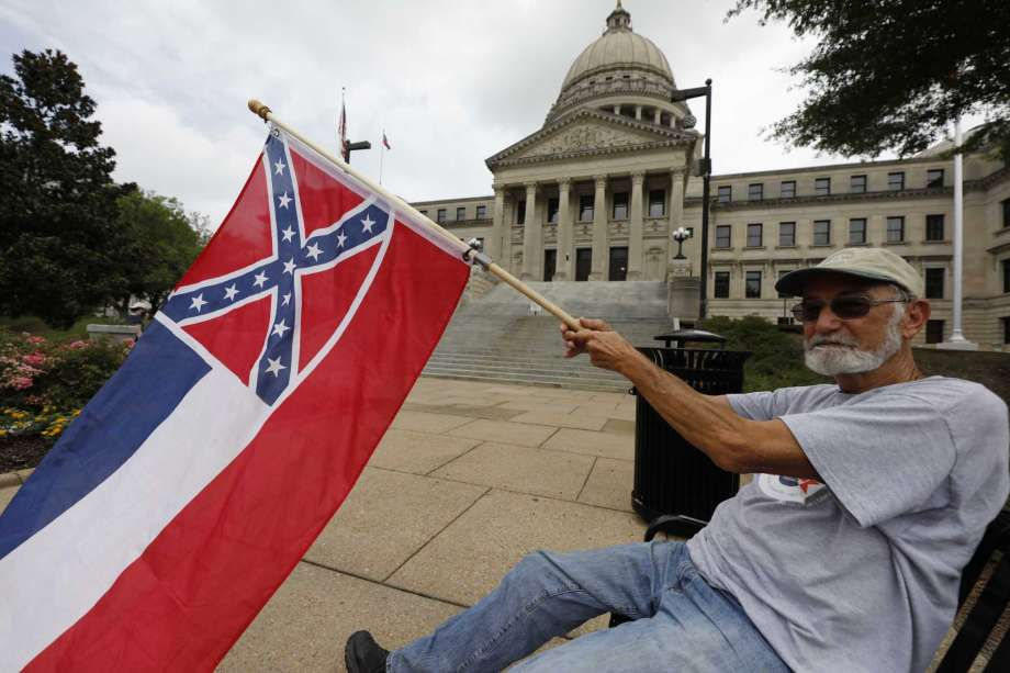 Larry Eubanks of Star waves the current Mississippi state flag as he sits before the front of the Capitol, Saturday, June 27, 2020, in Jackson, Miss. While a supporter of the current flag, Eubanks says he would hope lawmakers would allow a proposed flag change to be decided by the registered voters. The current state flag has in the canton portion of the banner the design of the Civil War-era Confederate battle flag, that has been the center of a long-simmering debate about its removal or replacement. Photo: Rogelio V. Solis, AP / Copyright 2020 The Associated Press. All rights reserved