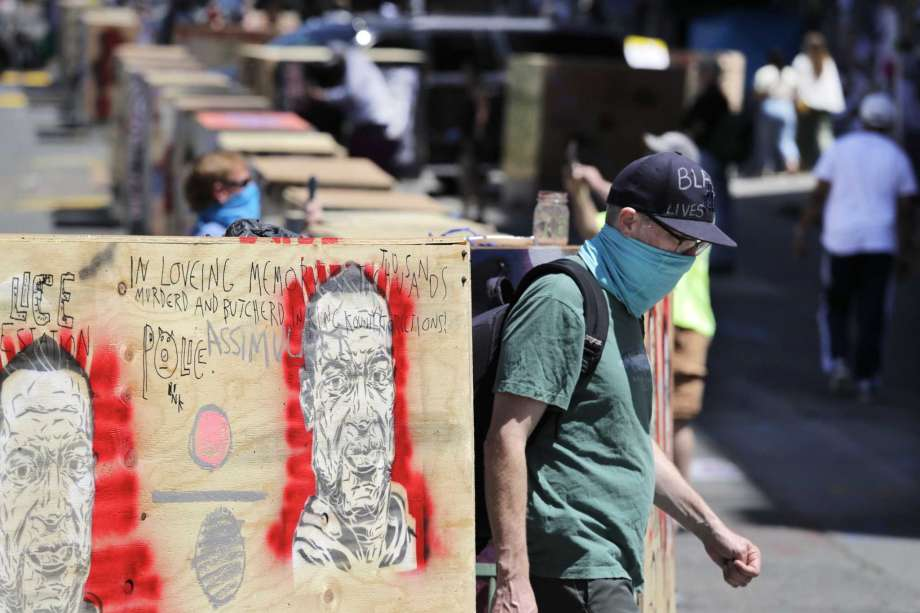 A man walks between barricades blocking a street adjacent to a closed police precinct Thursday, June 18, 2020, in Seattle, in what has been named the Capitol Hill Occupied Protest zone. Police pulled back from several blocks of the city's Capitol Hill neighborhood near the Police Department's East Precinct building earlier in the month after clashes with people protesting the death of George Floyd in Minneapolis. Photo: Elaine Thompson, AP / Copyright 2020 The Associated Press. All rights reserved