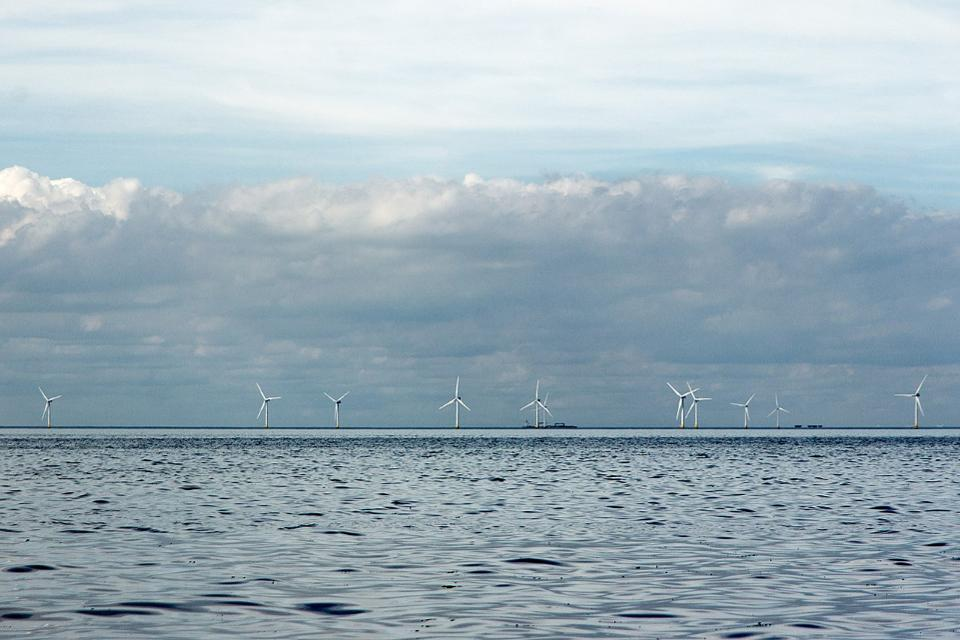 Windmills turning in the North Sea under a cloudy sky.
