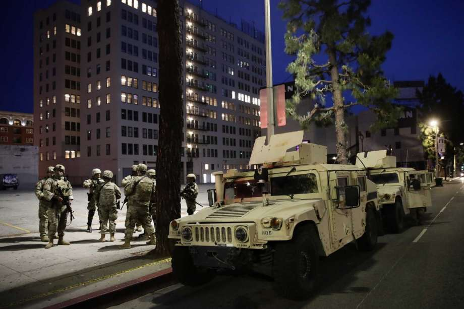 National Guardsmen stand next to Humvees as protests over the death of George Floyd continue Sunday, May 31, 2020, in Los Angeles. Armed National Guard soldiers lined the steps of Los Angeles City Hall and cities across California declared curfews Sunday to head off more violence after unruly demonstrators at earlier protests burned police cars, broke into stores and skirmished with officers. Photo: Jae C. Hong, AP / Copyright 2020 The Associated Press. All rights reserved.