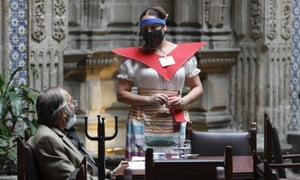 A waitress at Mexico City's iconic Sanborns of the Azulejos restaurant, wearing a mask and face shield.